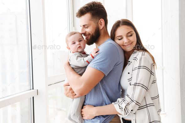 Pleased loving couple parents holding in hands their little son. - Stock Photo - Images