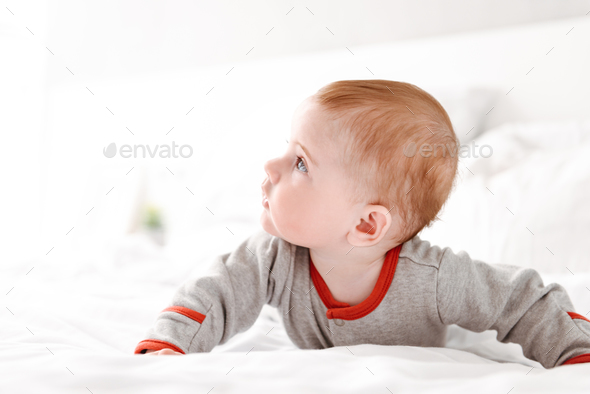 Cute little baby child lies on bed indoors at home. - Stock Photo - Images