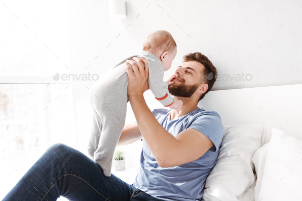 Young man father dad having fun with his little baby - Stock Photo - Images