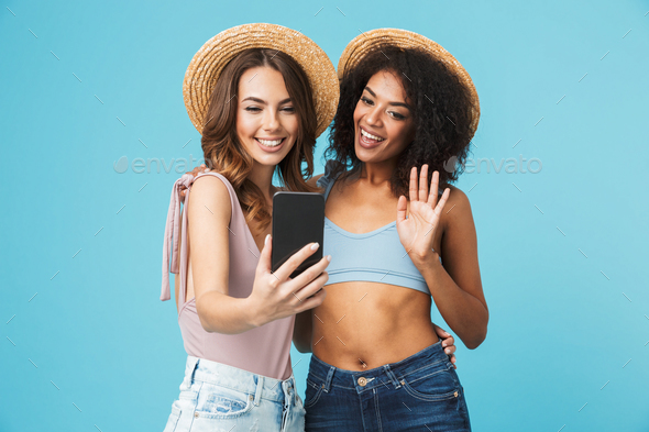 Vacation photo of two multiethnic girls wearing straw hats and s - Stock Photo - Images