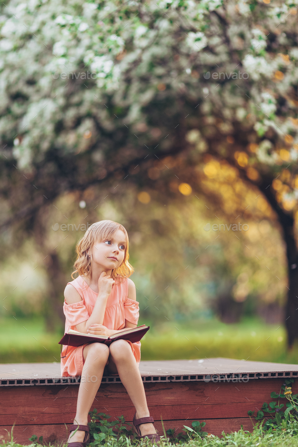 Dreaming little girl with a book - Stock Photo - Images