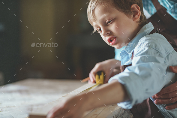 Dad and son measuring the board - Stock Photo - Images