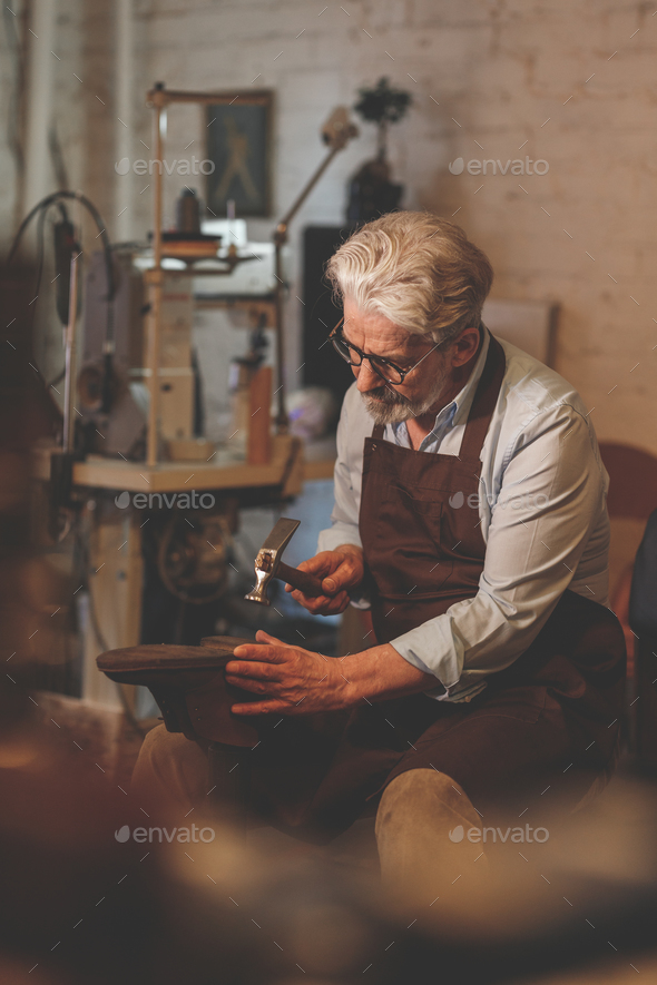 An elderly shoemaker in studio - Stock Photo - Images
