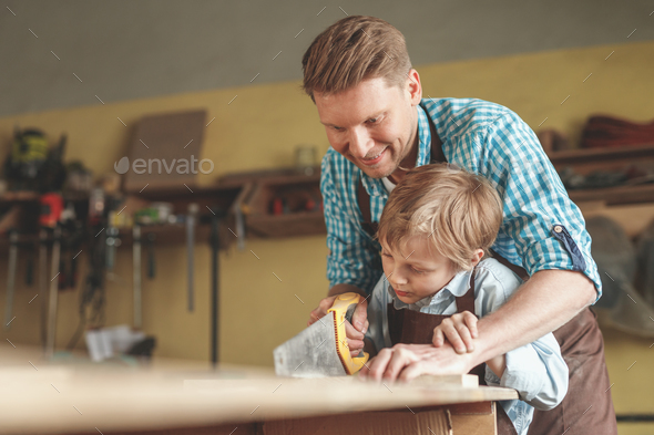 Father and son sawing a board indoors - Stock Photo - Images