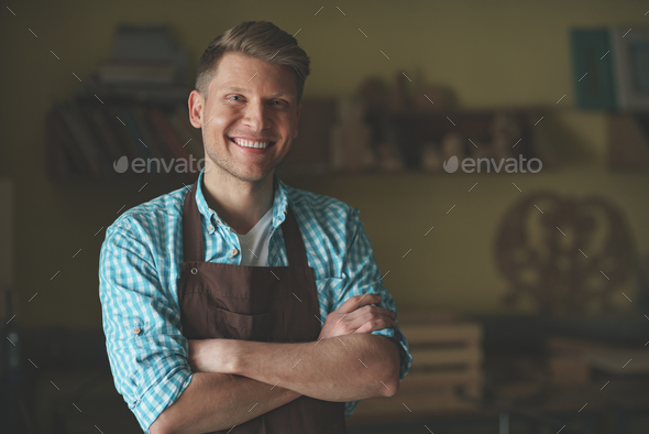 Young master in an apron in carpentry - Stock Photo - Images