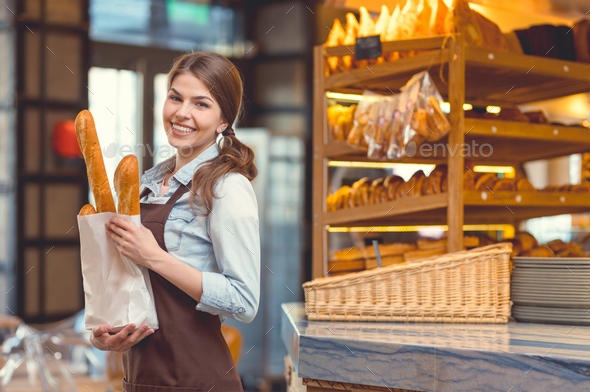 Young smiling girl with baguettes - Stock Photo - Images