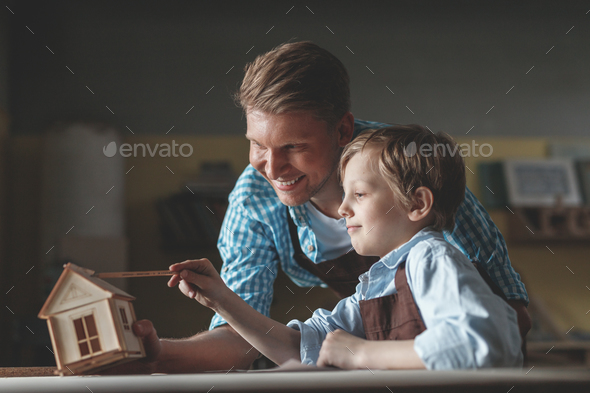Smiling father and son with a wooden house - Stock Photo - Images