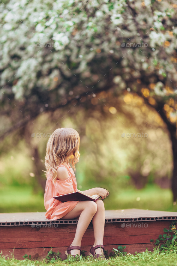 Little girl with a book outdoors - Stock Photo - Images