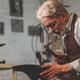 An elderly shoemaker in uniform at work - PhotoDune Item for Sale