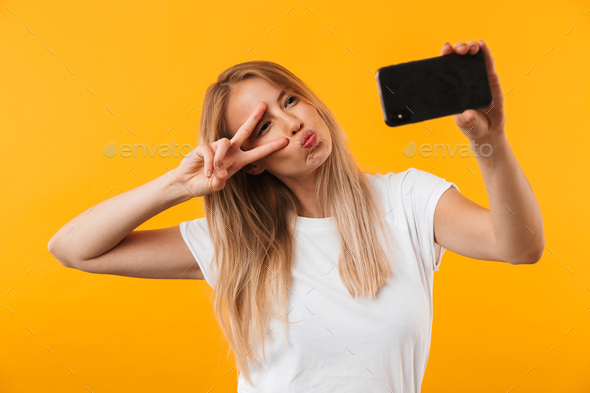 Happy young blonde girl showing peace gesture - Stock Photo - Images