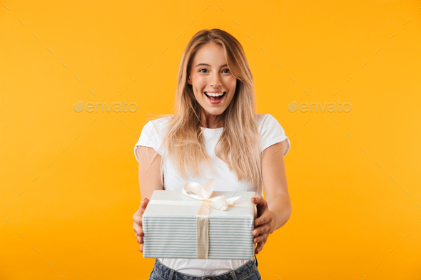 Portrait of a cheerful young blonde girl giving present box - Stock Photo - Images