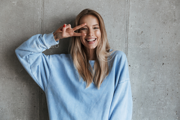 Young cheerful happy pretty woman showing peace gesture. - Stock Photo - Images