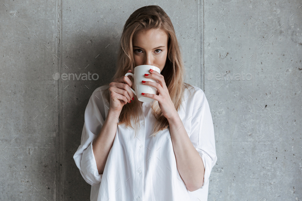Cute young woman indoors over grey wall drinking coffee - Stock Photo - Images