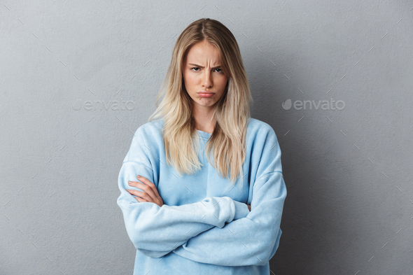 Portrait of an upset young girl in blue sweatshirt - Stock Photo - Images