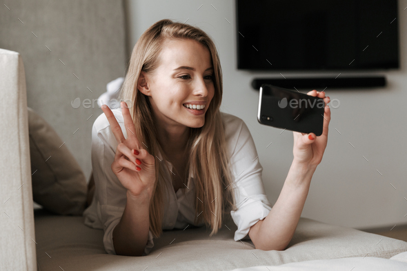 Happy cute young woman lies indoors - Stock Photo - Images
