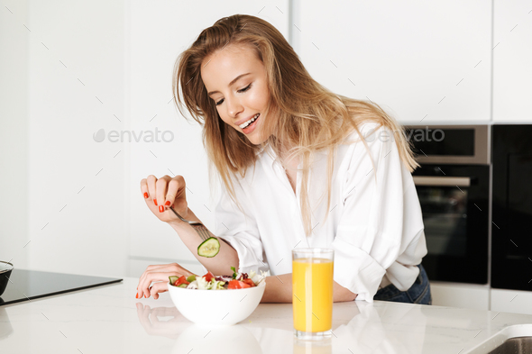 Smiling young woman eating salad from a bowl - Stock Photo - Images