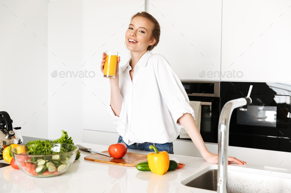 Beautiful woman standing in kitchen drinking juice. - Stock Photo - Images