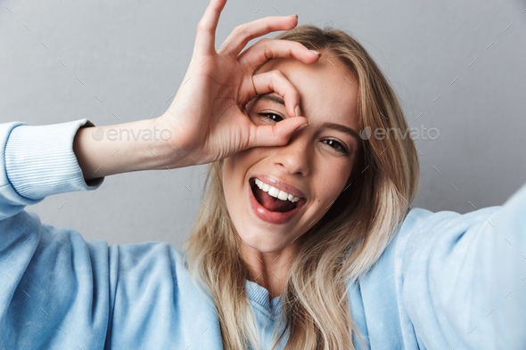 Close up of smiling young blonde girl taking a selfie - Stock Photo - Images