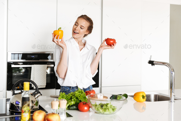 Beautiful woman standing in kitchen cooking - Stock Photo - Images