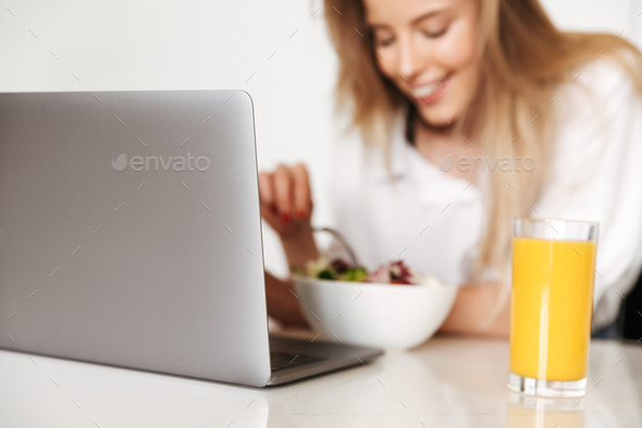 Close up of happy woman eating salad - Stock Photo - Images