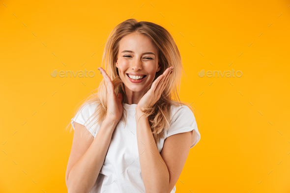 Portrait of a happy young blonde girl jumping - Stock Photo - Images