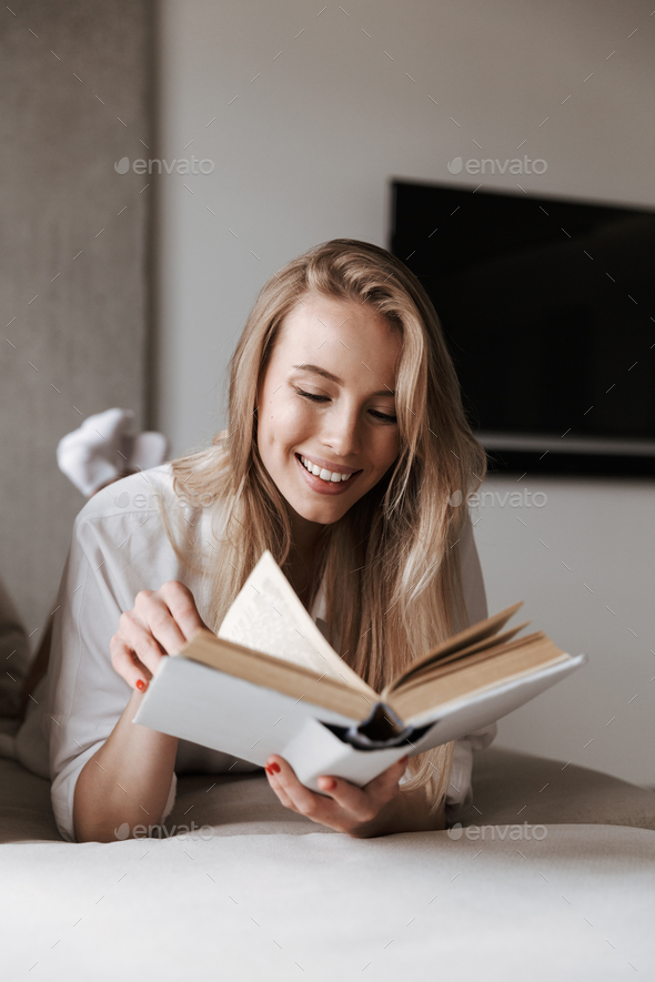 Cheerful young woman reading blank cover open book - Stock Photo - Images