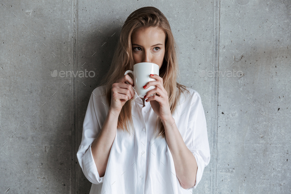 Woman indoors over grey wall drinking coffee holding cup. - Stock Photo - Images