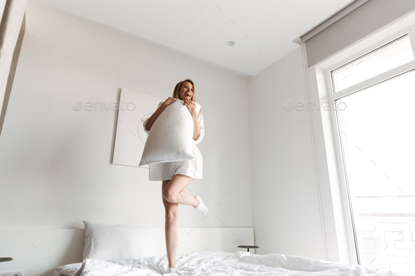 Happy pretty woman jumping with pillow - Stock Photo - Images
