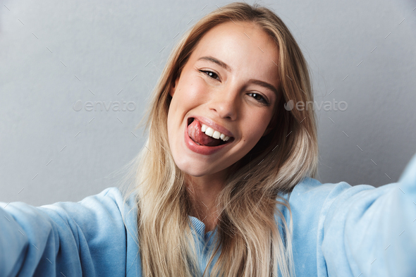 Close up of cheerful young blonde girl taking a selfie - Stock Photo - Images