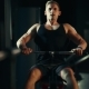 A Muscular Man Performs Exercises on the Back Muscles in a Dark Gym, Lifting Weights - VideoHive Item for Sale