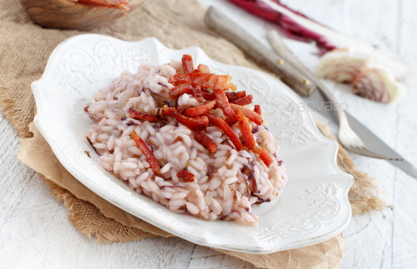 Risotto with red radicchio and crispy bacon (speck) - Stock Photo - Images