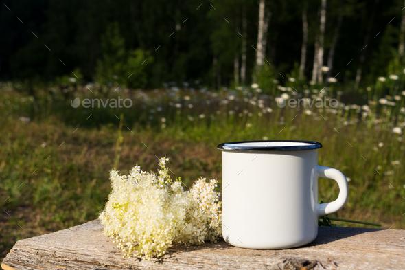 White campfire enamel mug mockup with white flowers - Stock Photo - Images