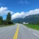 Driving a Car on a Road in Norway In the Background, the Biker Rides a Motorcycle - VideoHive Item for Sale