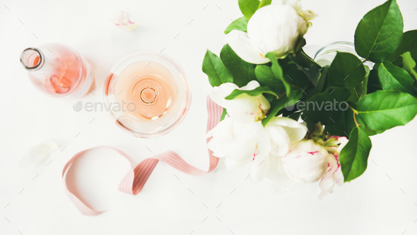 Rose wine, decorative ribbon and peony flowers over white background - Stock Photo - Images