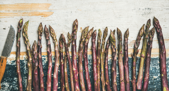 Fresh Raw uncooked purple asparagus over rustic wooden background - Stock Photo - Images