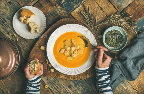 Fall warming pumpkin cream soup with seeds and bread croutons - Stock Photo - Images