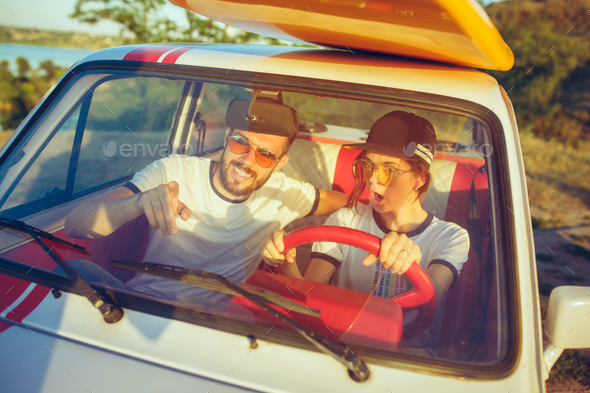Laughing romantic couple sitting in car while out on a road trip at summer day - Stock Photo - Images