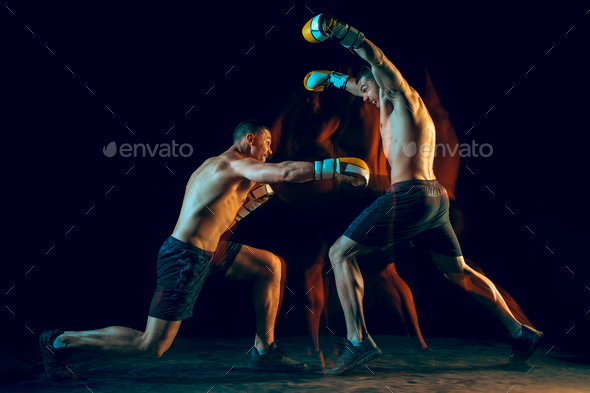 Male boxer boxing in a dark studio - Stock Photo - Images
