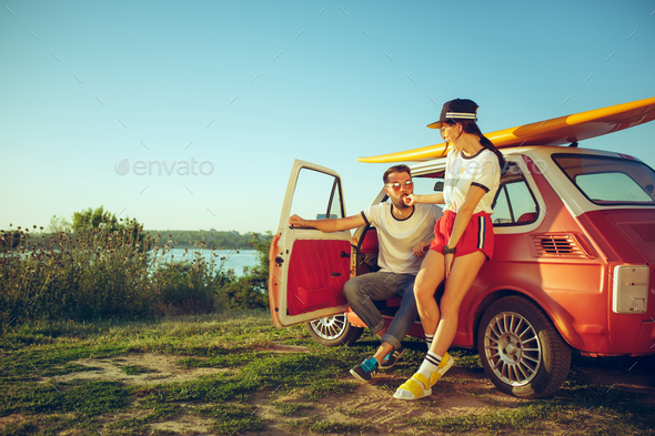 Couple resting on the beach on a summer day near river - Stock Photo - Images