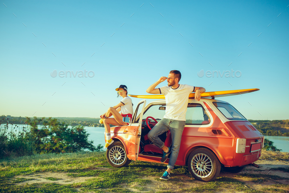 Couple sitting and resting on the beach on a summer day near river - Stock Photo - Images