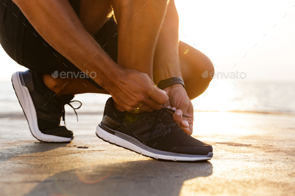 Cropped photo legs of sporty caucasian man in tracksuit and snea - Stock Photo - Images