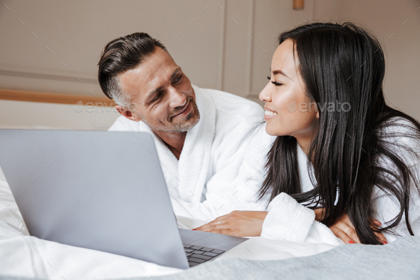 Image of multiethnic couple man and woman wearing white bathrobe - Stock Photo - Images