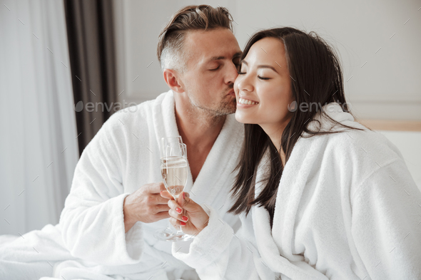 Image of caucasian handsome man kissing beautiful asian woman on - Stock Photo - Images
