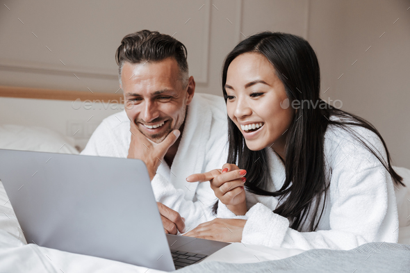 Happy young couple dressed in bathrobes lying on bed - Stock Photo - Images