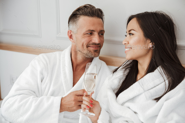 Romantic couple 30s caucasian man and asian woman wearing white - Stock Photo - Images