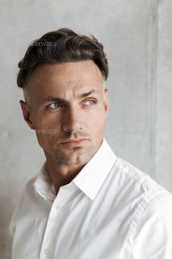 Close up portrait of a concentrated man in white shirt - Stock Photo - Images