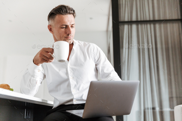 Successful man dressed in formal clothes using laptop - Stock Photo - Images
