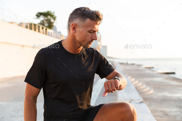 Photo of european muscular man 30s in tracksuit walking along bo - Stock Photo - Images