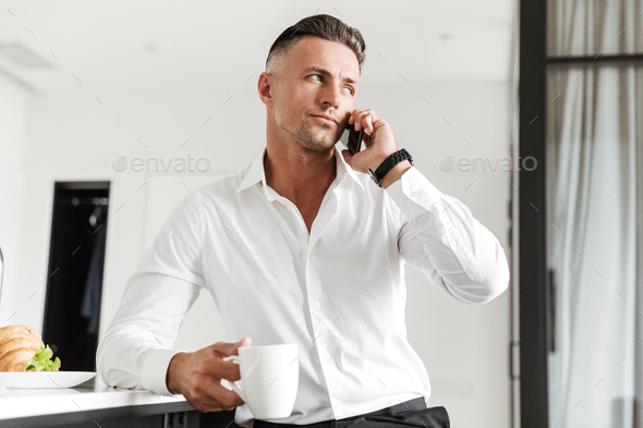 Smiling man dressed in formal clothes having breakfast - Stock Photo - Images