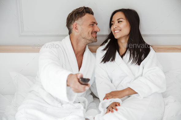Lovely couple 30s caucasian man and asian woman wearing white ho - Stock Photo - Images
